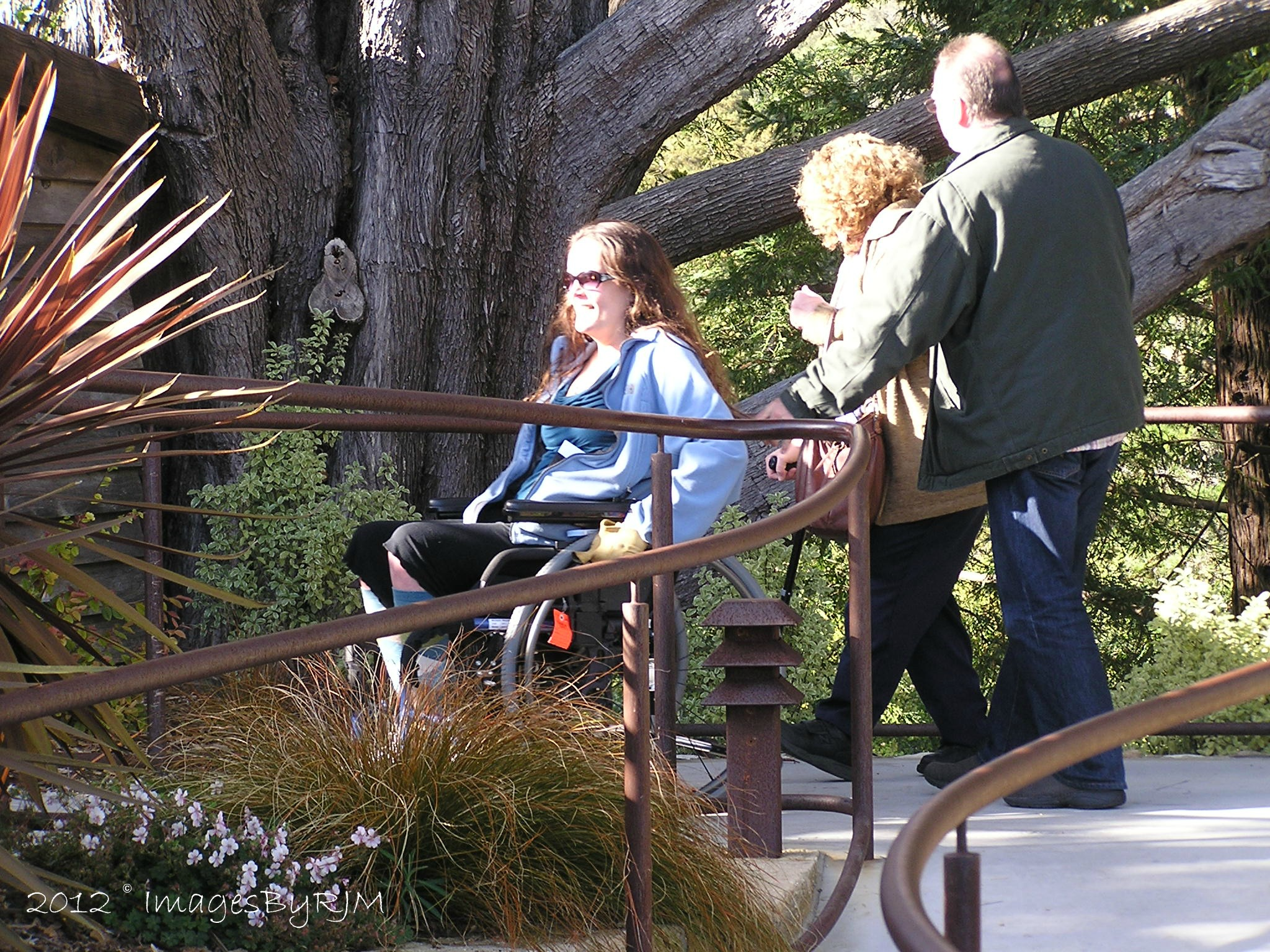 Three people, one in wheelchair, moving along outdoor walkway at Nepenthe Restaurant, Big Sur.