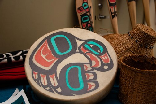 Drum, hats and paddles depicting Southeast Alaskan Native American culture.