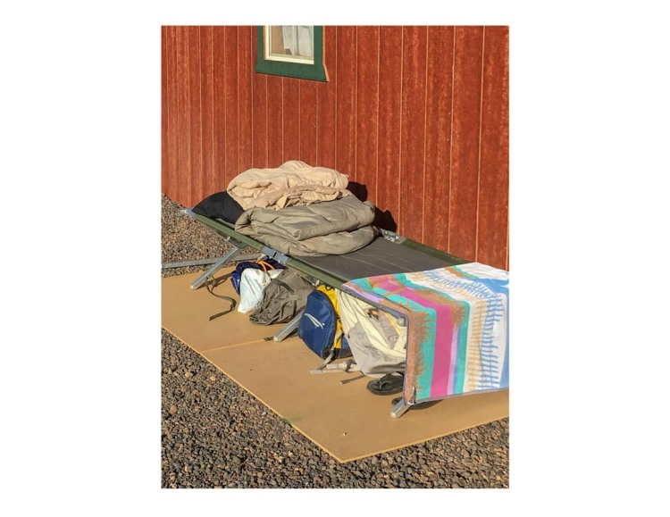 Sleeping cot with bedding on top and duffle bag and other camping gear underneath, set up next to wood-paneled building.