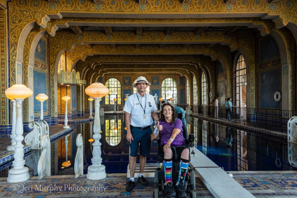 Male tour guide standing next to smiling woman in wheelchair, with elaborately decorated indoor pool at Hearst Castle in the background.