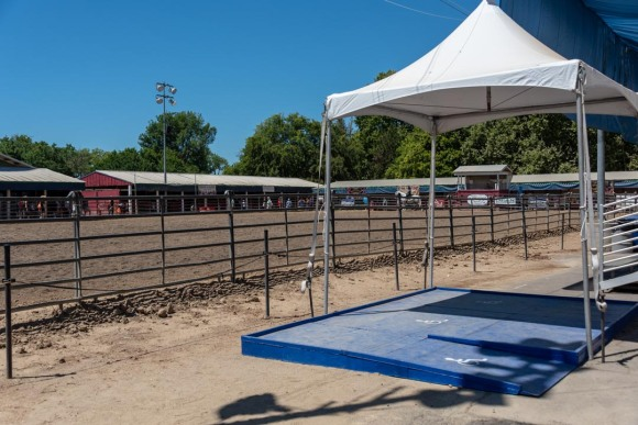 BLue handicap-accessible platform, with canopy above for shade, at edge of horse arena at California State Fair.