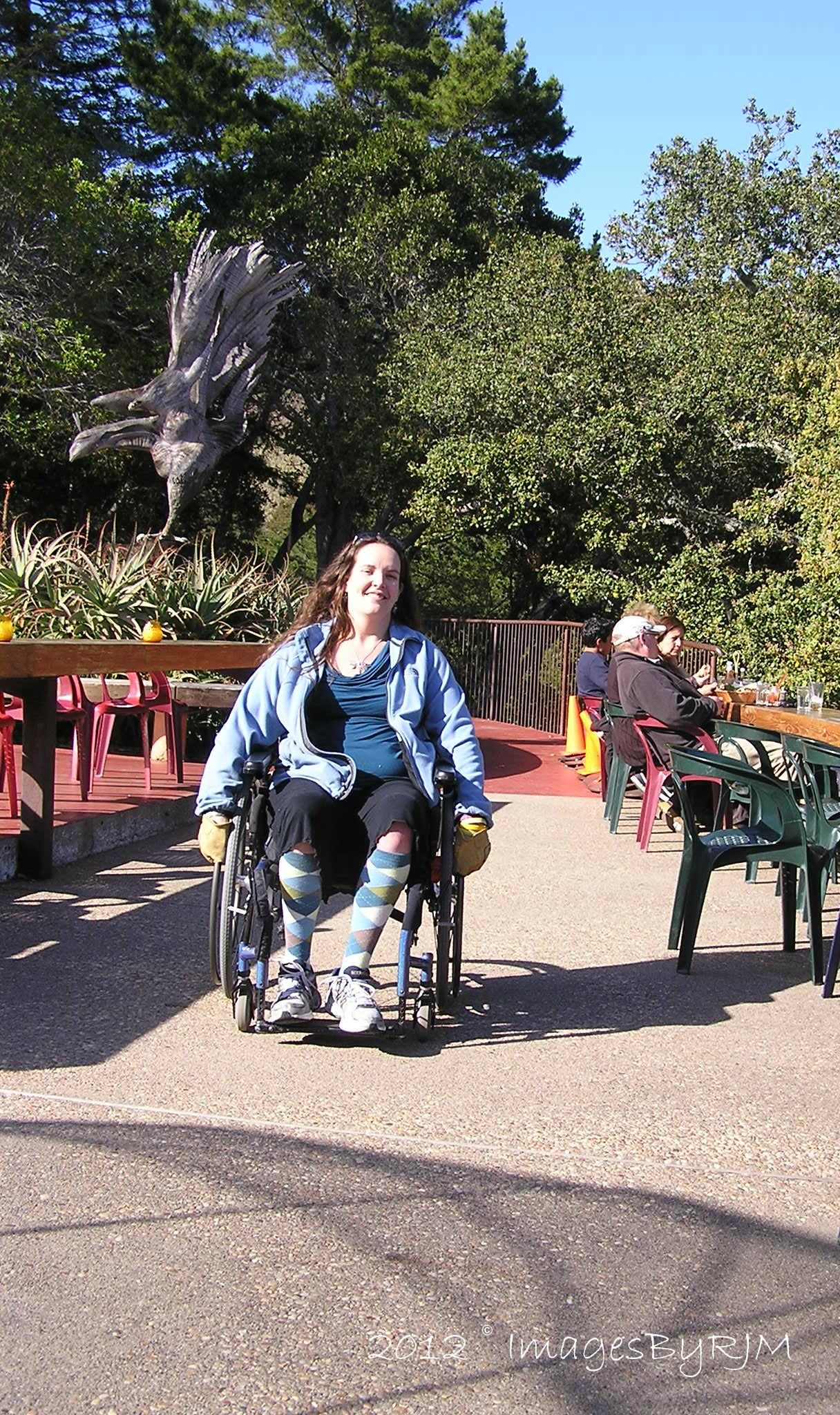 Woman in wheelchair on restaurant patio, with metal bird sculpture in background.