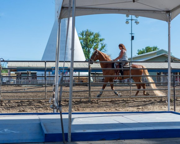 Woman riding horse in front of blue wheelchair-access platform at edge of horse arena at California State Fair.