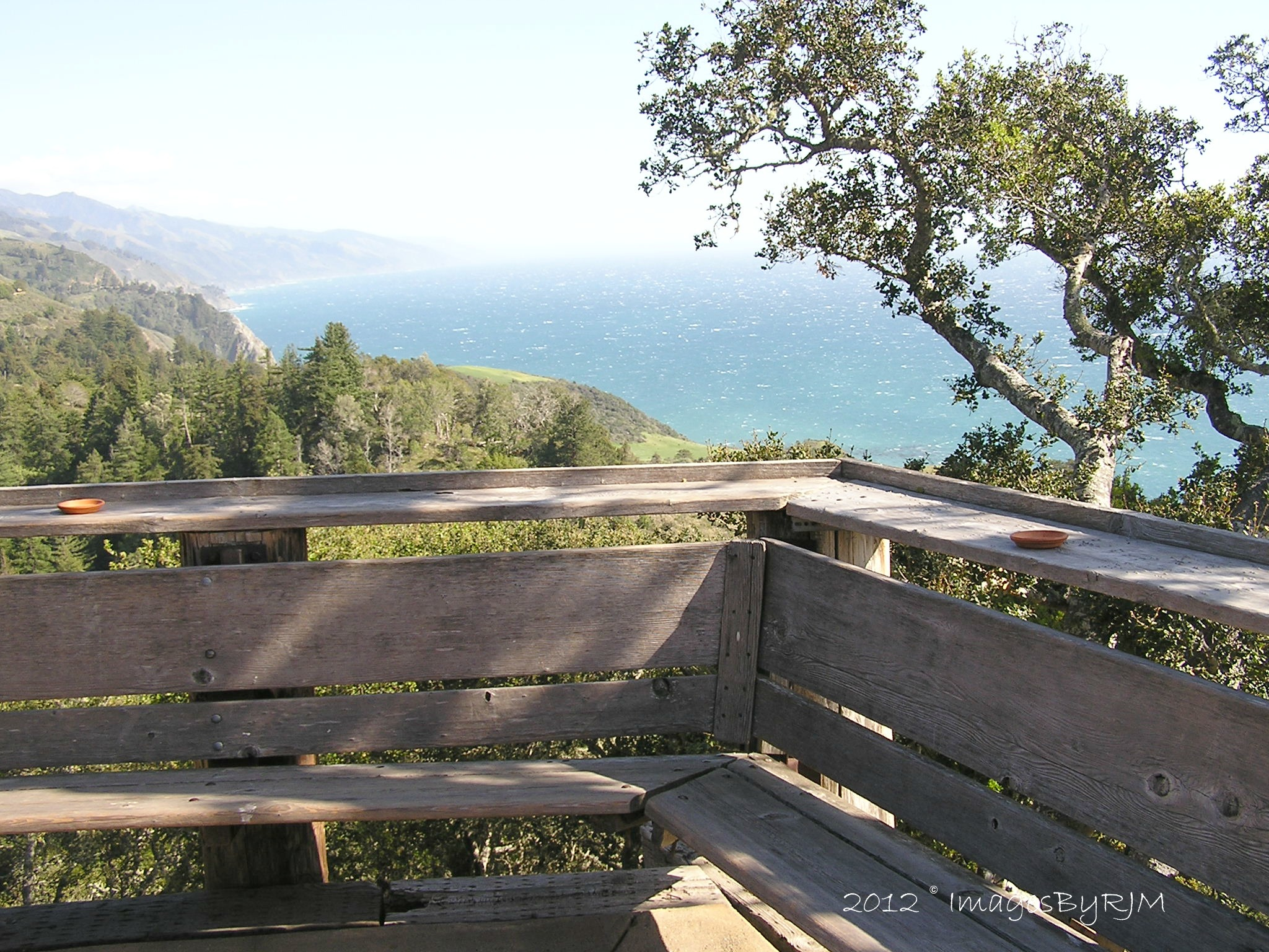 Wooden corner bench and railing overlooking Pacific Ocean from Nepenthe's Restaurant in Big Sur, California.