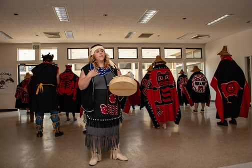 Southeast Alaska Native American woman drumming and speaking, with tribe members standing behind her.