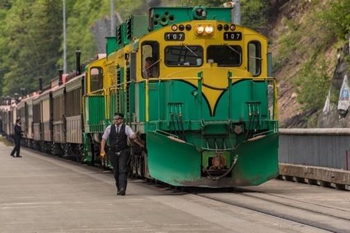 Conductor walking alongside train engine, stopped for passenger loading.