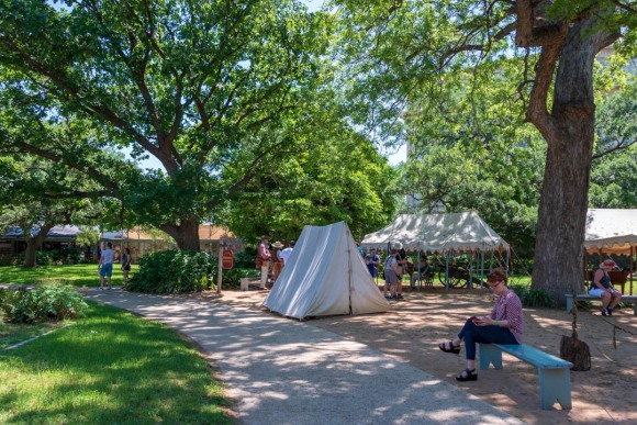 Tent used in reenactment of Alamo history, with visitors on landscaped grounds in background.