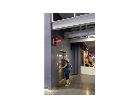 Woman standing at elevator door inside building at California State Fair.