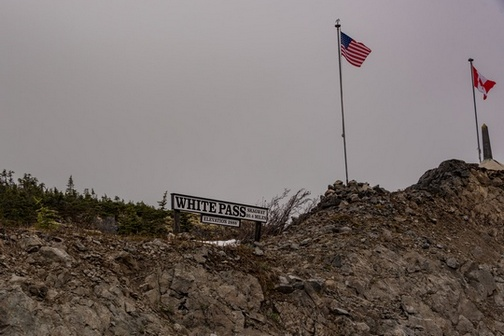 "American and Canadian flags flying next to ""White Pass Scenic Railway"" sign on hillside."