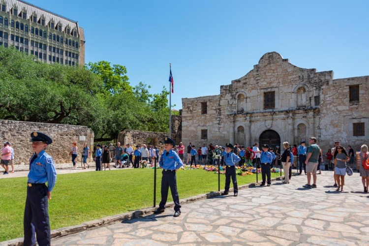 Young men standing at attention while tourists and visitors enter the chapel of the Alamo.