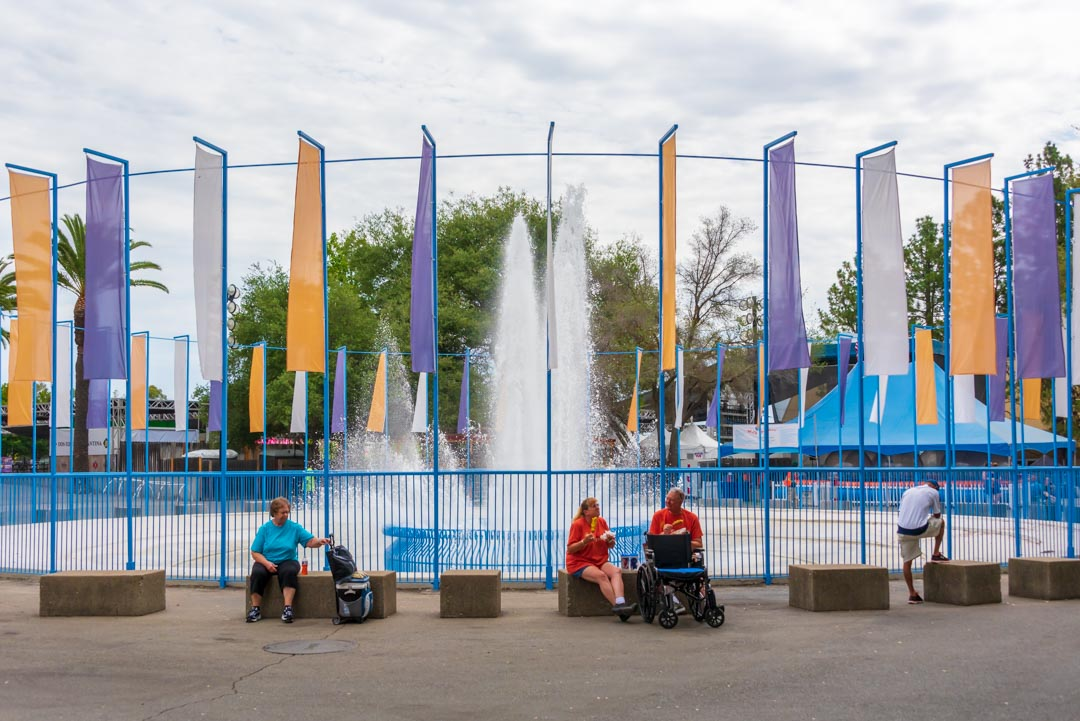 Wheelchair users sitting in front of large fountain and eating corn dogs at California State Fair.