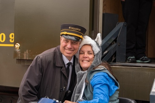 Closeup of uniformed train conductor and hood-wearing passenger, both smiling for camera.