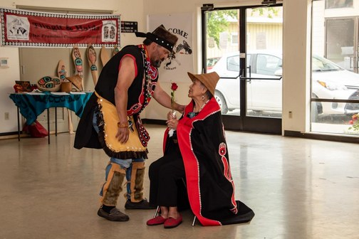 Southeast Alaska Native American man presenting rose to seated elderly Native American woman.