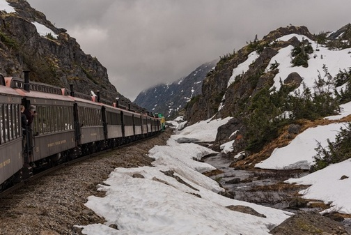 White Pass Scenic Railway train cars traveling along rocky mountainside, with snow and stream along the side of the route.