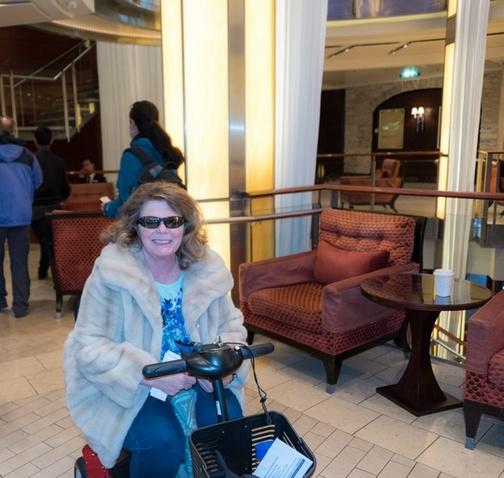 Adult woman wearing fur coat and sunglasses, sitting in mobility scooter inside cruise ship lobby.