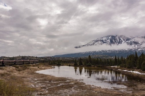 Landscape image of snow-capped mountains, cloudy grey skies, small pond next to evergreen trees, and train cars in the background.