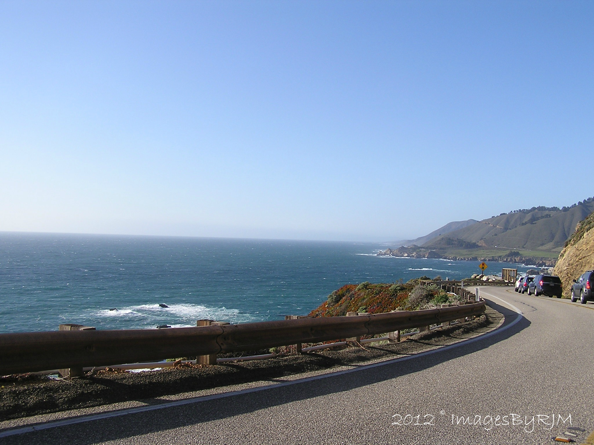 Traffic stopped on Pacific Coast Highway between Big Sur and Carmel, with view of ocean to the left.