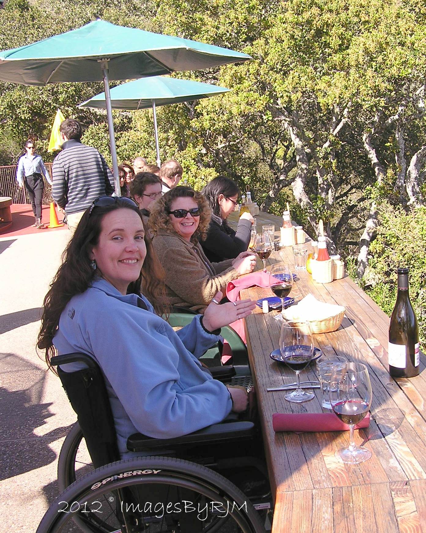 Woman in wheelchair, and her friend, smiling and sitting at wooden restaurant deck.