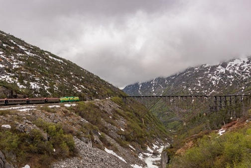 View of White Pass Scenic Railway train cars traveling along White Pass mountainside, with old wooden train bridge and snowy mountains in background.
