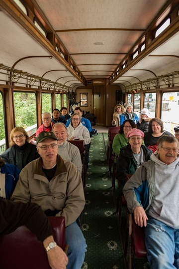 View of smiling adult passengers sitting in seats inside narrow train car.