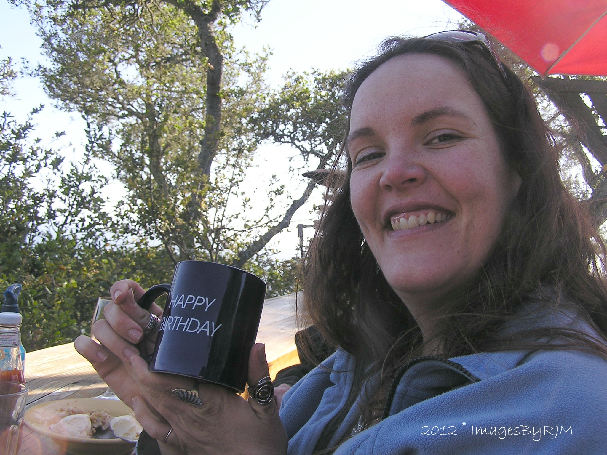 "Smiling young woman holding ""Happy Birthday"" coffee mug."