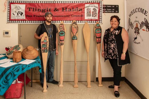 Young man and his mother standing beside hand-crafted Southeast Alaska Native American cedar canoe paddles.