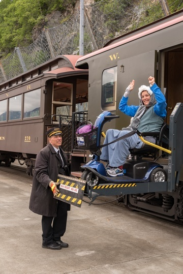 Train conductor using hydraulic lift to transport woman in mobility scooter out of train car.