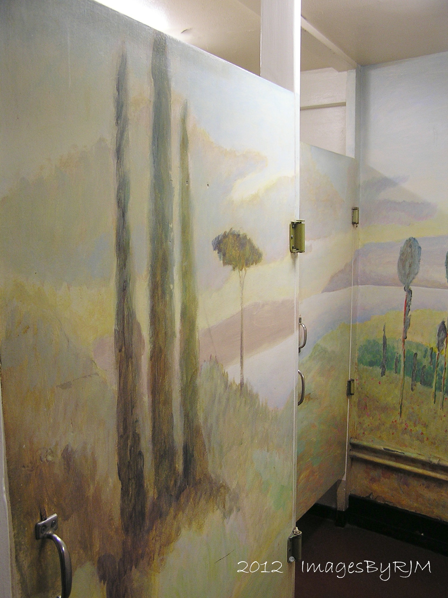 Mural-painted restroom stall door and wall at Nepenthe Restaurant.