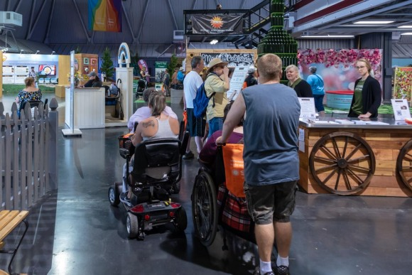 Line of wheelchair users, seen from behind, inside one of the exhibit buildings at California State Fair.