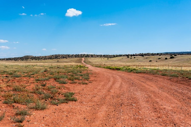 Landscape image of red dirt road in foreground, with small hills and vast blue sky in background.