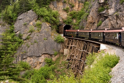 View of a section of a train crossing wooden trellis and entering tunnel into mountain.