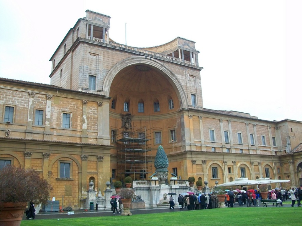 Exterior courtyard of Vatican Museum, with people holding umbrellas and looking at artifacts in background, and grassy area in foreground.