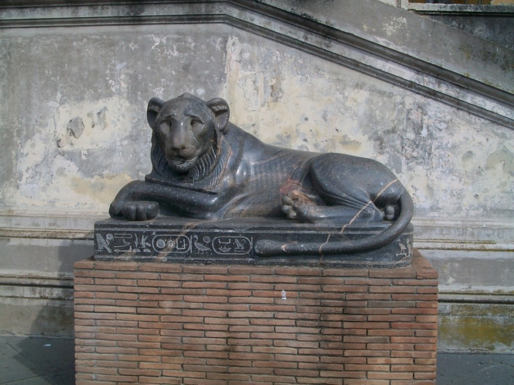 Reclining bronze lion on bronze and brick pedestal with Egyptian hieroglyphics carved on pedestal stand.
