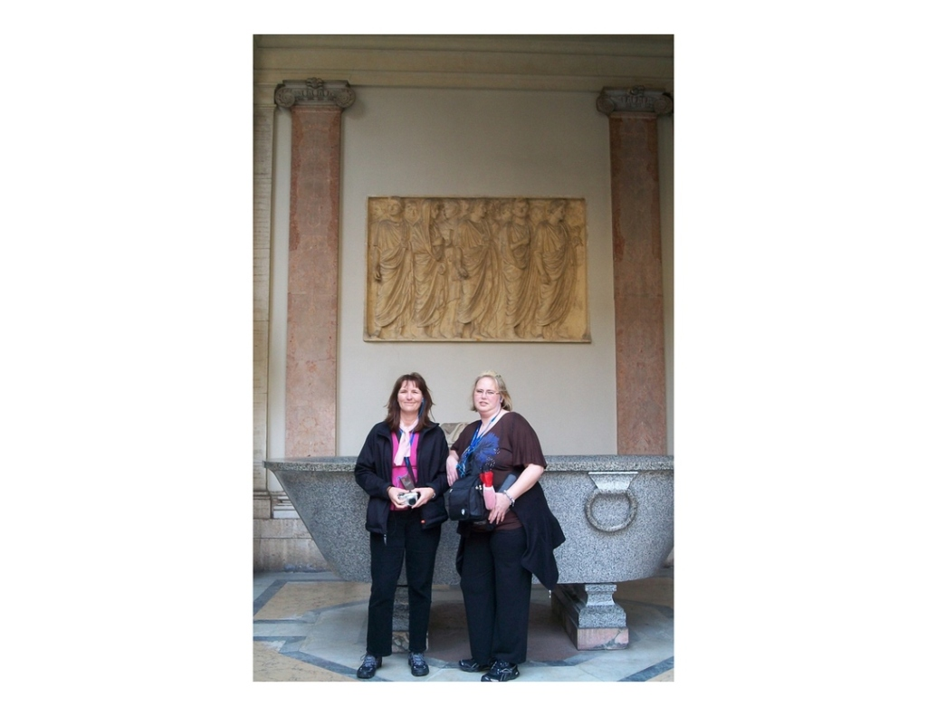 Two women standing beside large granite basin, with gold bas relief art on wall in courtyard of Vatican Museum.
