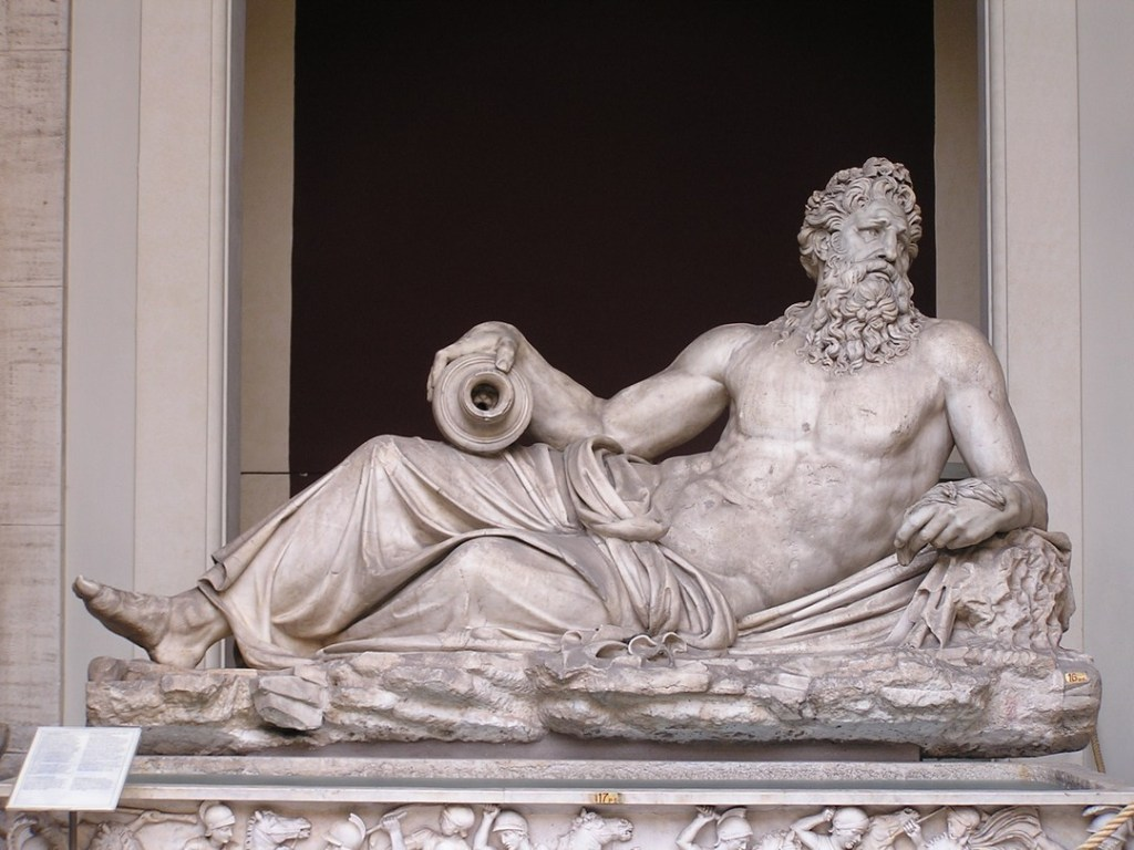 Marble status of reclining man - Bacchus - at the Vatican Museum.