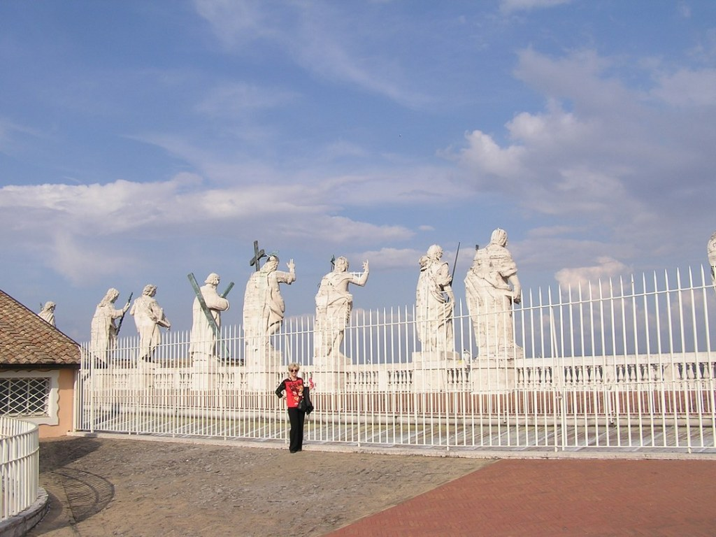 Blond woman in foreground standing next to white metal fence, with large marble statues of saints in background.