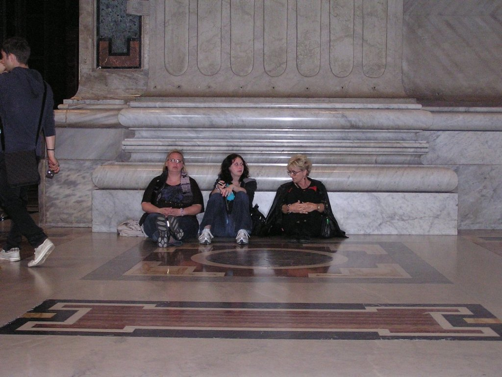 Three women seated on floor next to marble column in St. Peter's Basilica.