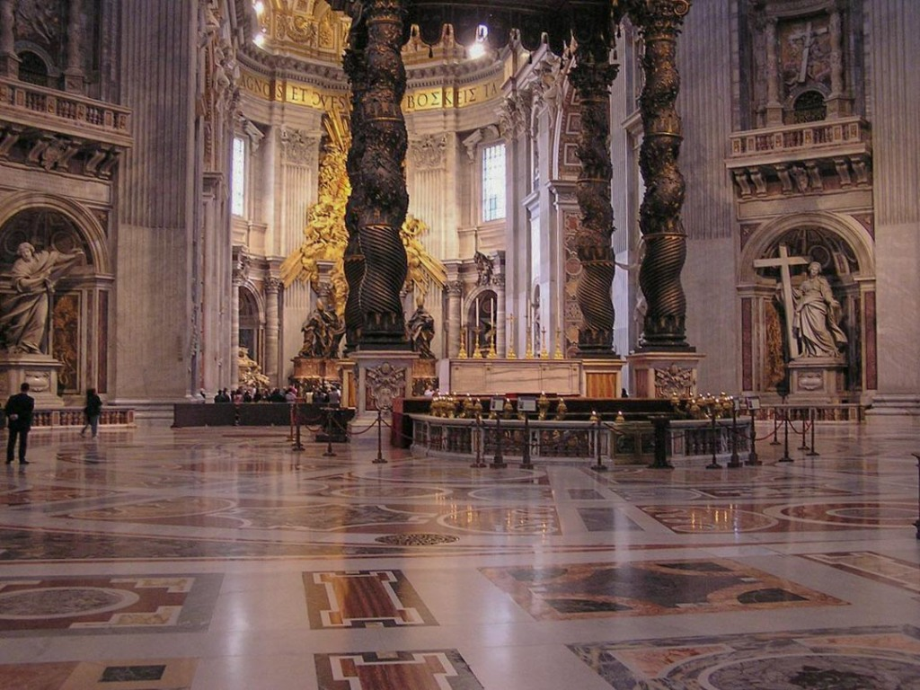 Interior of St. Peter's Basilica, showing vastness of size, the ornate gold altar, as well as the marble walls and floor and religious statues.