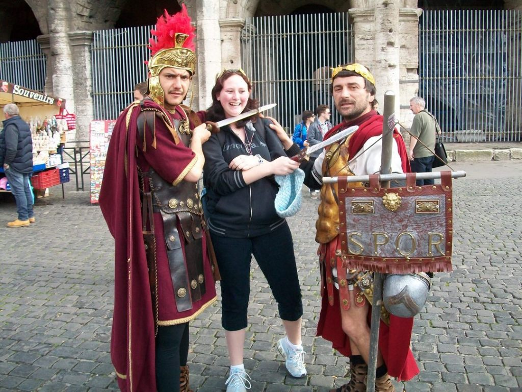 Two men, dressed as Roman centurians, posing with smiling young woman in front of Roman Colosseum.