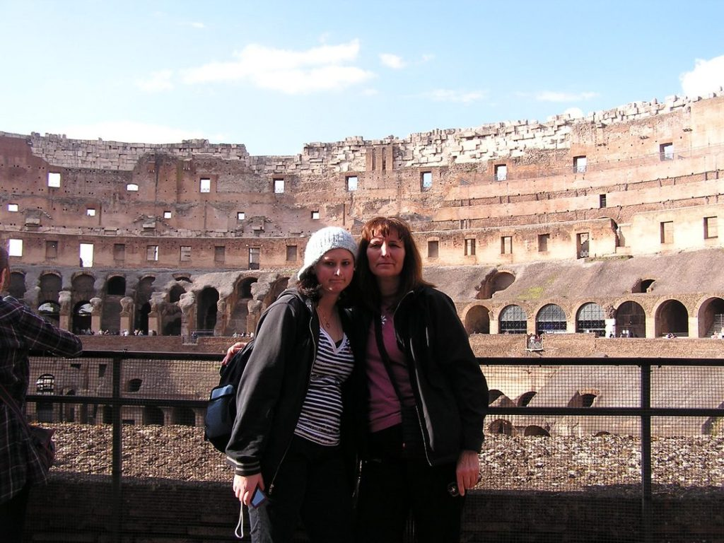 Two female tourists standing close together, with interior of Roman Colosseum in background.