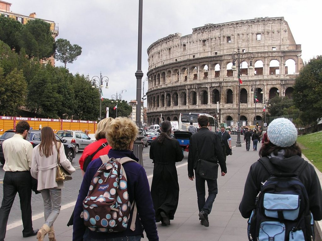 View of the Colosseum in Rome, taken from the pedestrian sidewalk with tourists in the foreground walking toward it.